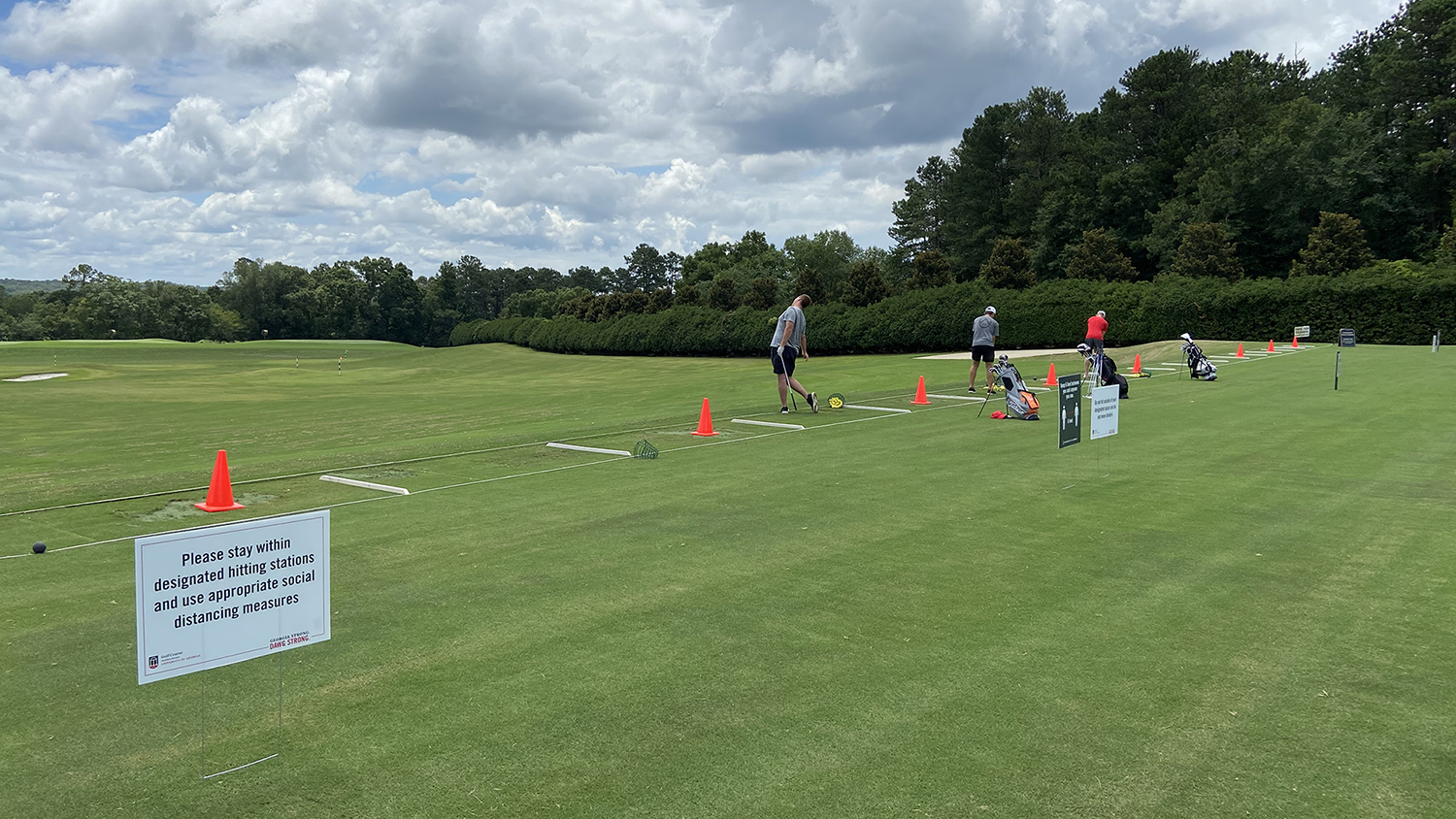 "Image of golfers at the driving range, separated into every other station by orange cones. A sign reads ""Please stay within designated hitting stations and use appropriate social distancing measures."""