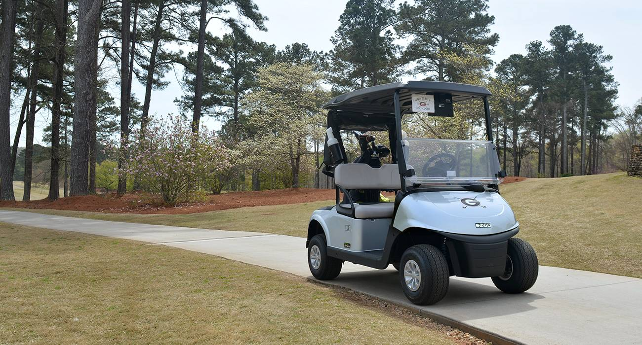 Photo of a golf cart on a path on the course with the UGA Golf Course logo on the front.