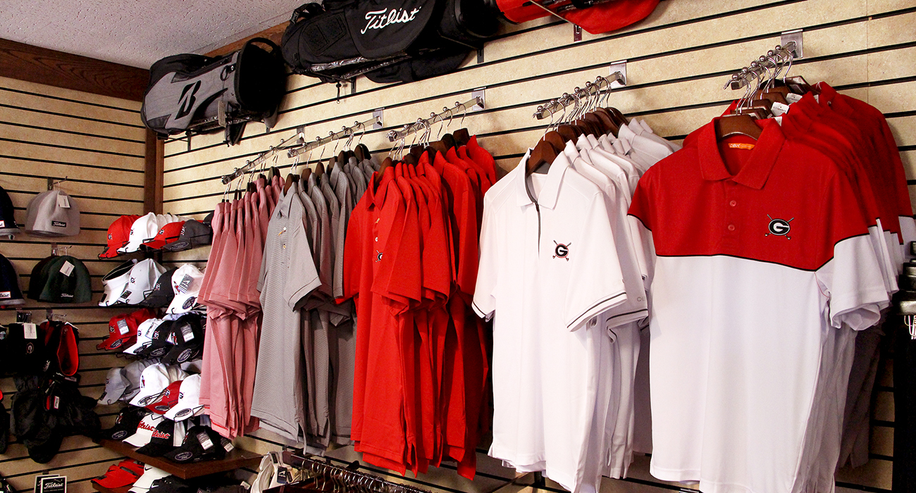 Photo of a display of golf bags and UGA Golf Course branded shirts and hats inside of the Golf Shop.
